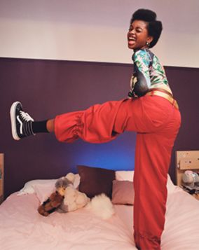 Sasha standing on bed with one leg raised